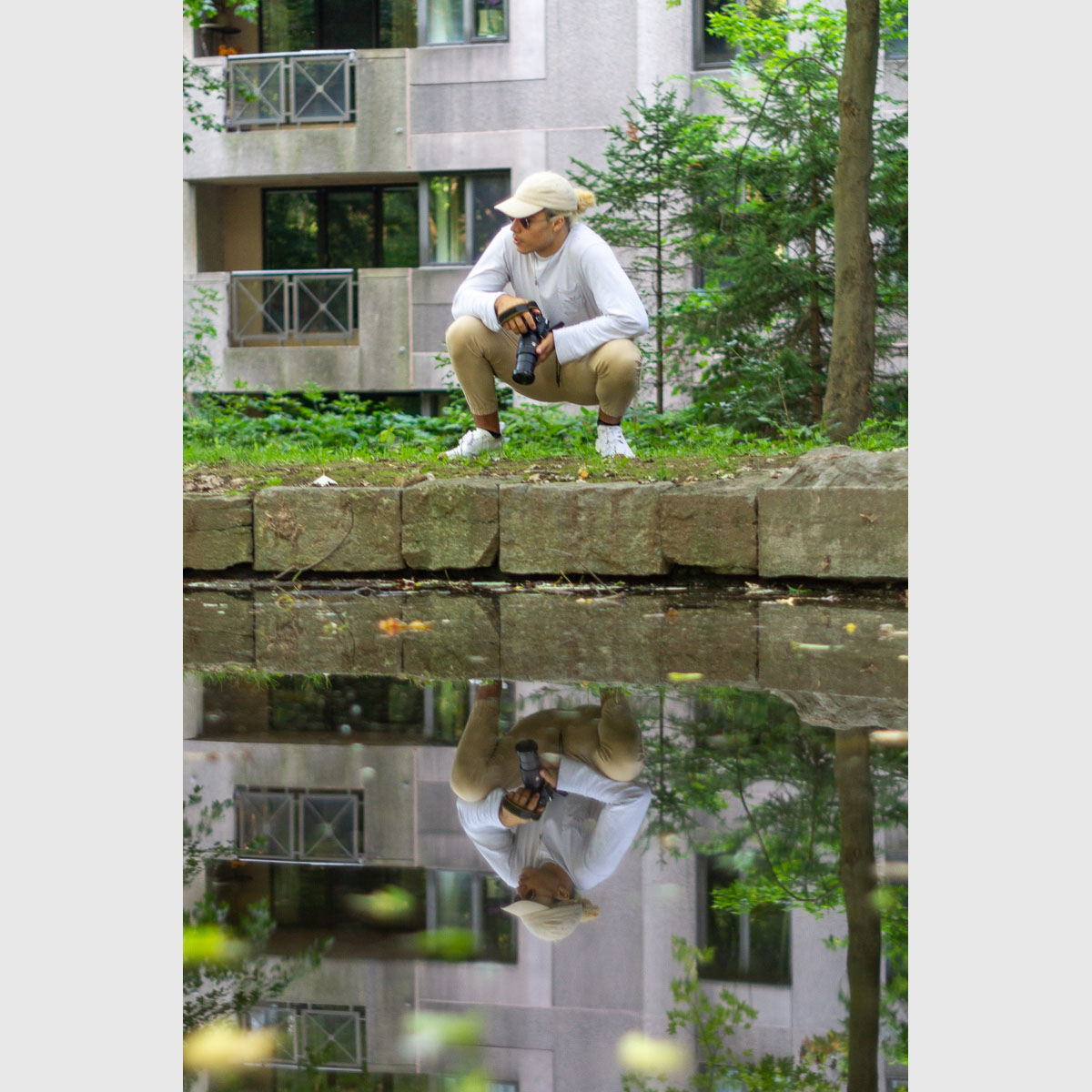 Tim Claude reflected in water, ready to snap some pics
